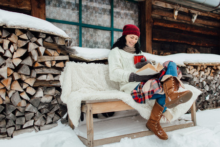 Winter relax - woman sitting outside a cottage and reading a book on a snowy day