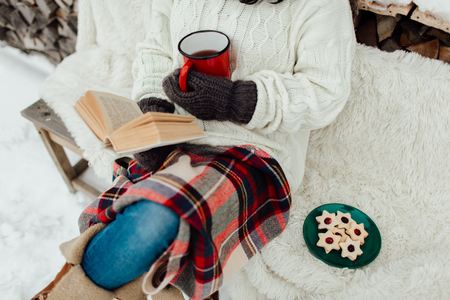 Cropped image of a woman enjoying reading a book on a cold winter day