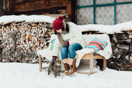 Woman and a cat relaxing outside a country house on a cold winter day