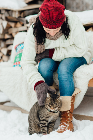 Portrait of a woman playing with her kitten outside a cottage on a cold winter day