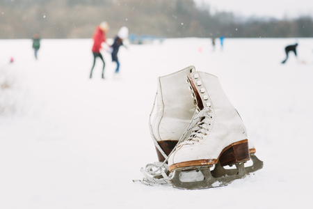 A pair of female ice skates lying on the snow with skaters in the background Фото со стока