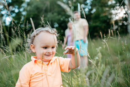 A happy little child touching grass stems. A portrait of a smiling toddler boy exploring nature and his parents watching  him. Фото со стока