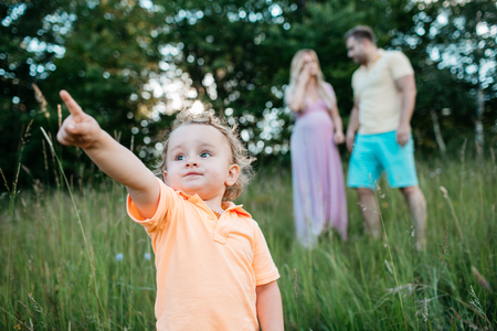 A portrait of a child pointing. A small boy standing on a field and pointing his index finger up.