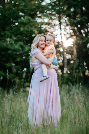 A pregnant woman holding her young son in her arms. A portrait of a smiling expecting mother and her toddler boy cuddling in a field at sunset. Фото со стока - 100370473
