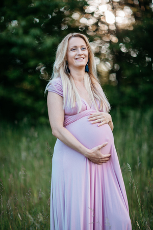 A young expectant mother gently touching her pregnancy belly. A portrait of a smiling pregnant woman enjoying being in the nature on a summer evening. Фото со стока