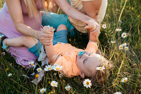 A small child lying in a field of daisies playing with his parents. A toddler boy resting in grass holding hands of his mother.