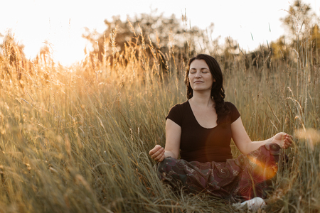 A portrait of a woman sitting in a tall grass with her eyes closed and meditating at sunset. A woman relaxing in the nature.