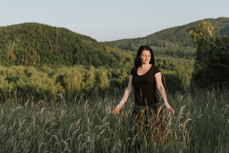 A portrait of a woman walking on her own through tall grass. A woman enjoying touching grass.