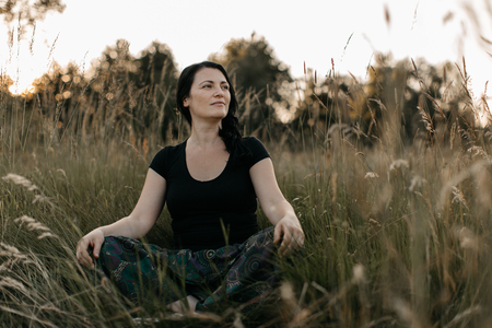 A portrait of a woman sitting cross legged in tall grass looking into distance. A woman enjoying being in the nature. Фото со стока