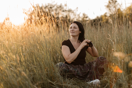 A portrait of a happy woman sitting in grass and doing her hair. A young woman enjoying plaiting hair in the nature at sunset. Stok Fotoğraf