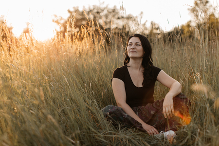 A portrait of a cheerful woman sitting cross legged in tall grass and enjoying sunset. A happy woman resting in the nature. Фото со стока - 103147271