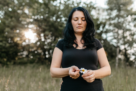 A portrait of a woman counting the petals on a daisy. A woman plucking a petal from a white daisy flower. Фото со стока - 103306429