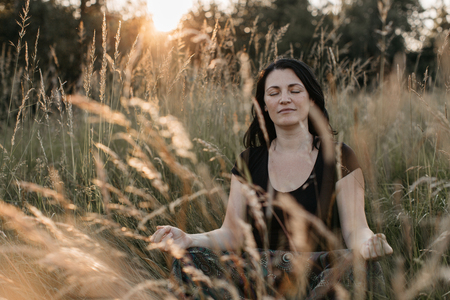 A portrait of a woman sitting in tall grass with her eyes closed and meditating at sunset. A woman relaxing in the nature.