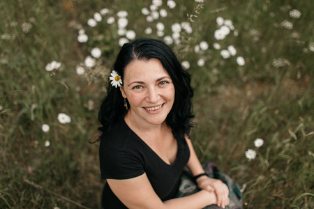 A high angle view of a young smiling woman sitting in grass wearing a daisy flower behind ear. A close up of a cheerful woman relaxing in the nature. Фото со стока - 103306426