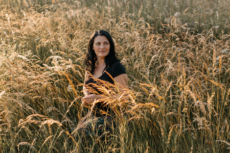 A portrait of a smiling woman sitting in a tall grass at sunset. A woman meditating in the nature.
