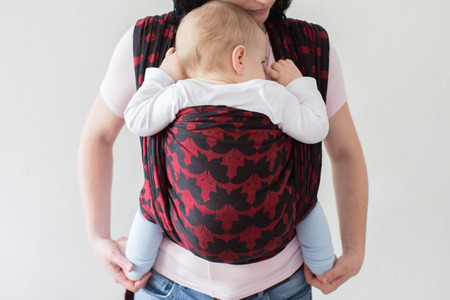 A cropped view of a baby in a woven wrap. A front view of a babywearing mother carrying her small child in a sling.