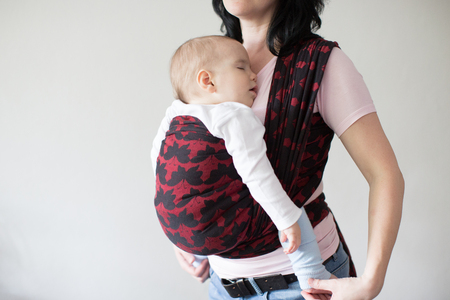 A cropped view of a baby in a woven wrap. A babywearing mother carrying her sleeping child in a sling. Фото со стока - 103825639