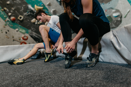 Couple of climbers sitting on a mat and getting ready for indoor climbing. Cropped view of a man and woman putting on climbing shoes in an indoor bouldering gym. Фото со стока - 104699666