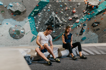 Cheerful young couple getting ready for indoor climbing. A front view of a man and woman sitting on a crash pad in an indoor bouldering gym. Фото со стока - 104699667