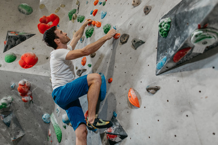 Boulderer climbing up a bouldering wall. A male climber making his way up an artificial climbing wall in an indoor bouldering gym.