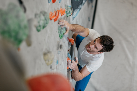 Male climber making his way up an artificial climbing wall in an indoor bouldering gym. A high angle view of a boulderer climbing up a bouldering wall. Фото со стока - 104699670