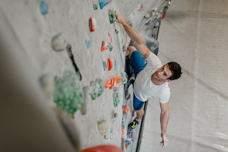 Male climber making his way up an artificial climbing wall in an indoor bouldering gym. A high angle view of a boulderer climbing up a bouldering wall. Фото со стока - 104699671
