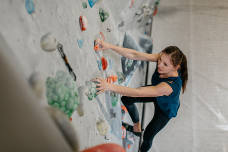 Female climber making her way up an artificial climbing wall in an indoor bouldering gym. A high angle view of a boulderer climbing up a bouldering wall. Фото со стока - 104699674