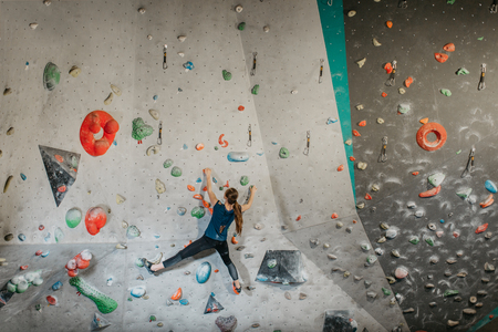 Female climber making her way up an artificial climbing wall in an indoor bouldering gym. A back view of a boulderer climbing up a bouldering wall.