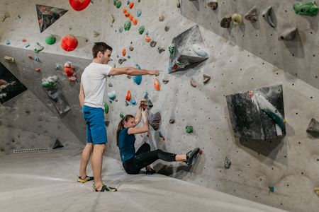 Bouldering instructor showing a way to a female trainee. Man and woman climbing in an indoor bouldering gym. Фото со стока - 104699676
