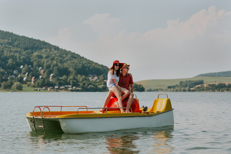 Portrait of smiling couple in love having fun pedal boating on hot summer day. Full length of young happy man and woman sitting on pedal boat.