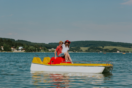 Portrait of smiling couple in love having fun pedal boating. Full length of young happy man and woman sitting on pedal boat.