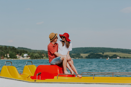 Portrait of smiling couple in love enjoying pedal boating. Girlfriend and boyfriend cuddling on pedal boat. Фото со стока