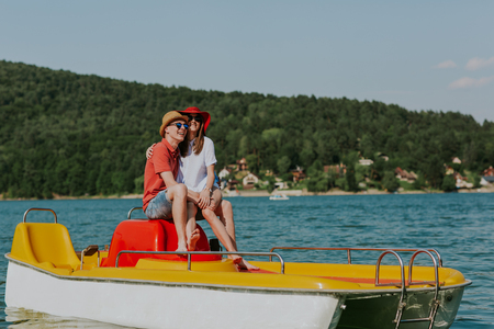 Shot of happy couple sitting on pedal boat. Young man and woman in love enjoying boating in the lake.
