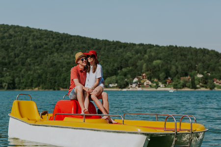Young lovers having fun in pedalo boat on hot summer day. Cheerful man and woman holding hands while boating on the sea. Фото со стока