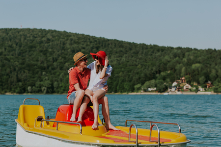 Couple in love laughing while boating in the lake. Portrait of young man and woman having fun pedal boating.