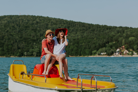 Couple in love laughing while boating in the lake. Portrait of young man and woman having fun pedal boating. Фото со стока - 106721602
