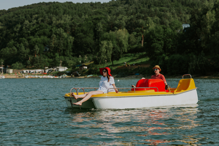 Couple in love enjoying boating in the lake. Portrait of young man and woman pedal boating on the river. Фото со стока