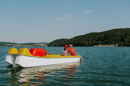 Rear view of couple sitting on pedal boat with feet in the water. Back view of man and woman enjoying boating on the lake on warm sunny day. Фото со стока