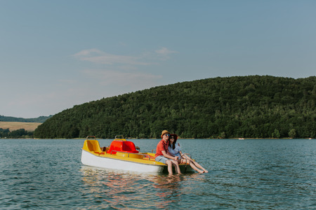 Couple in love resting on pedal boat with feet in water. Smiling man and woman hugging while boating on the lake. Фото со стока