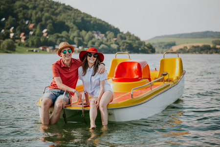 Front view of smiling young couple sitting on pedal boat. Portrait of man and woman in love enjoying boating on the lake.