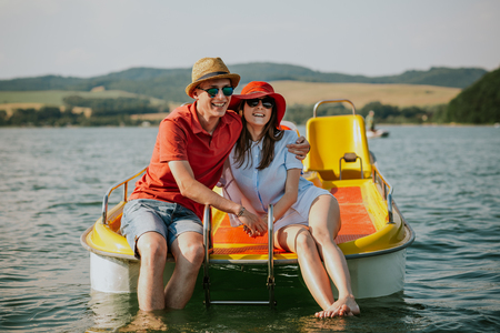 Front view of smiling young couple sitting on pedal boat. Portrait of man and woman in love enjoying boating on the lake. Фото со стока - 106721649
