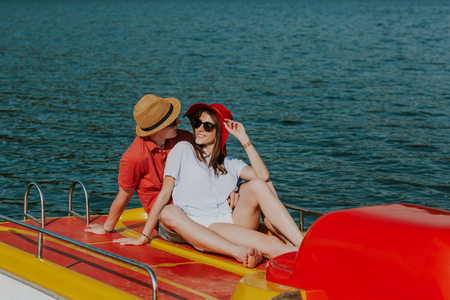 Cheerful man and woman cuddling while boating. Portrait of couple in love sharing tender moments on pedal boat on warm sunny day. Фото со стока