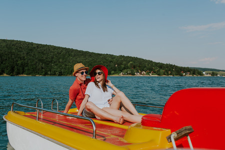 Cheerful man and woman having fun while boating. Portrait of couple in love enjoying being together on pedal boat on warm sunny day.