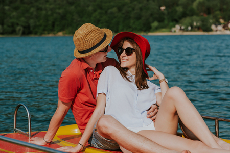 Cheerful man and woman having fun while boating. Portrait of couple in love enjoying being together on pedal boat on warm sunny day. Фото со стока - 106721652