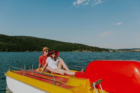 Cheerful man and woman having fun boating on the lake. Portrait of couple in love relaxing on pedal boat on warm sunny day.