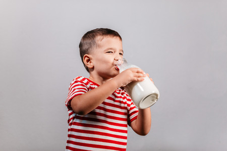 Portrait of young boy holding bottle of milk isolated over gray background - studio shot. Child drinking milk from glass bottle against grey background. Фото со стока