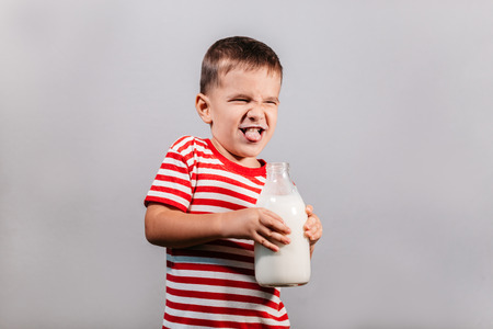 Child with bottle of milk against grey background. Portrait of young boy with milk mustache making faces isolated over gray background - studio shot.