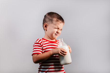 Front view of child with bottle of milk against grey background. Portrait of young boy with eyes closed making faces isolated over gray background - studio shot.