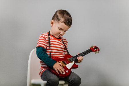 Child playing electric guitar. Portrait of young boy playing children acoustic guitar against grey background - studio shot.
