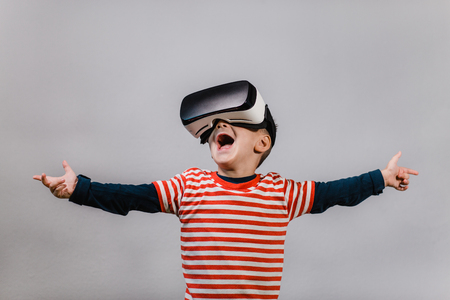 Portrait of happy child wearing virtual reality headset against grey background. Excited kid with hands spread having fun with VR glasses.